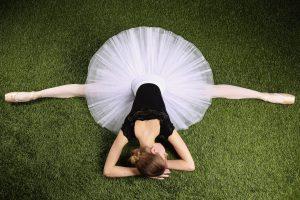 ballerina lying on grass doing the splits